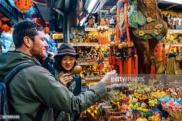 Mixed race couple shopping in outdoor Asian Market