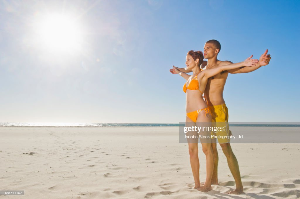 Mixed race couple standing together on beach : Stock Photo