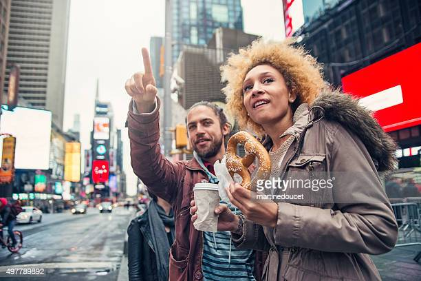 Mixed race couple visiting Times Square New York in autumn.