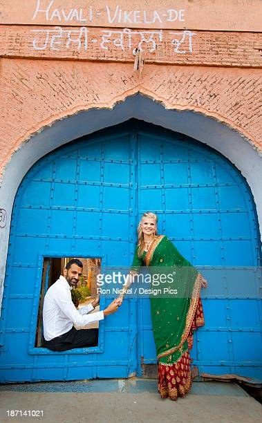 A Mixed Race Couple With Her Wearing A Sari At A Doorway With Large Blue Doors