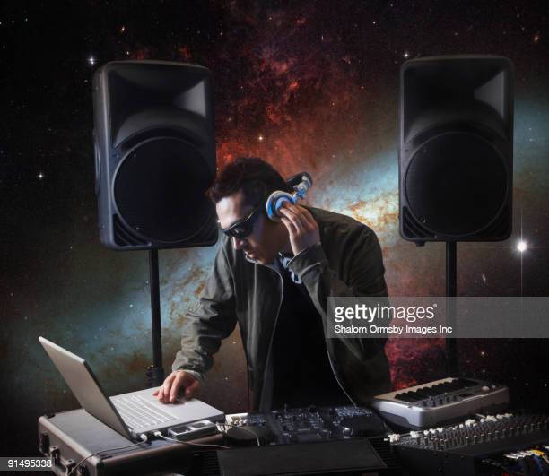 Mixed race DJ working with equipment