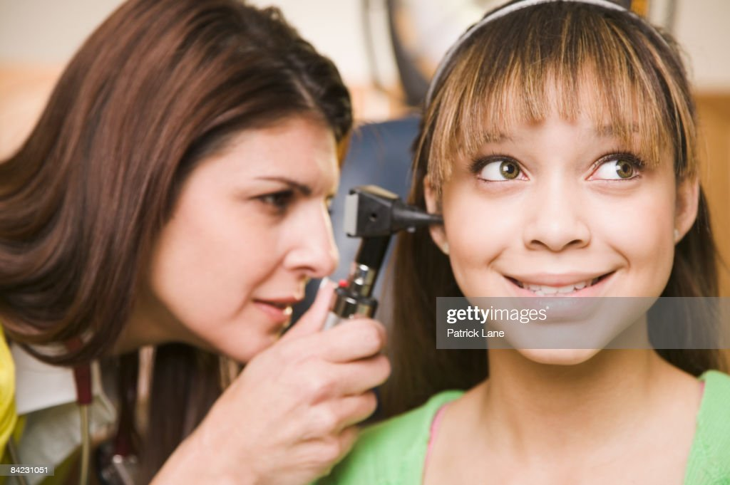 Mixed race doctor examining teenage girl's ears : Stock Photo