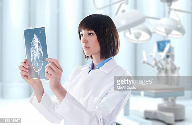 Mixed race doctor looking at digital tablet in operating room