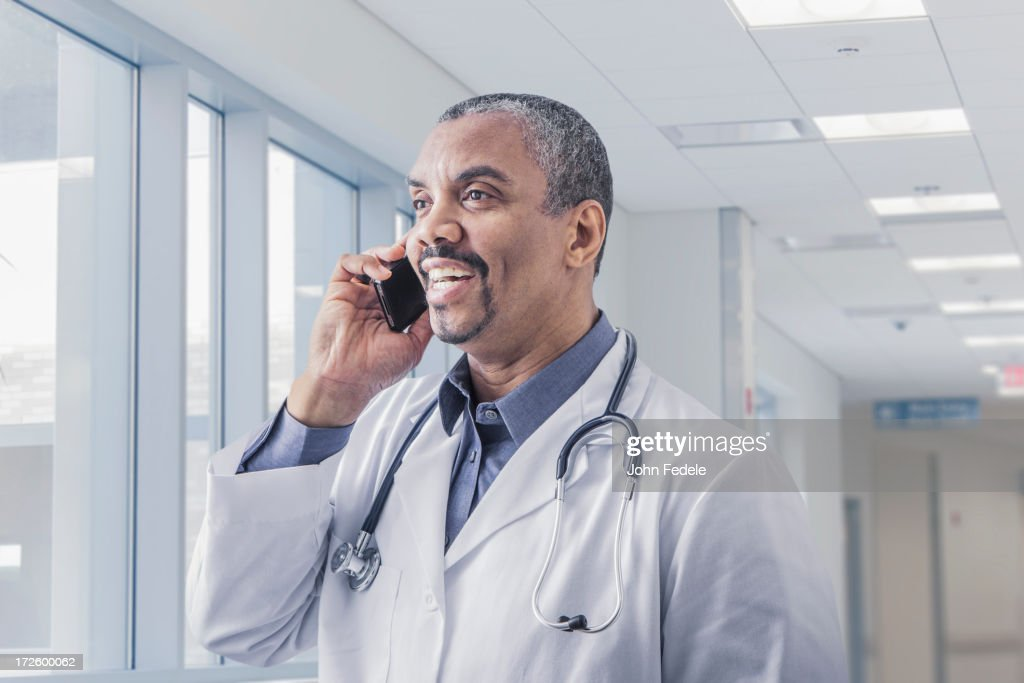 Mixed race doctor talking on cell phone in hospital