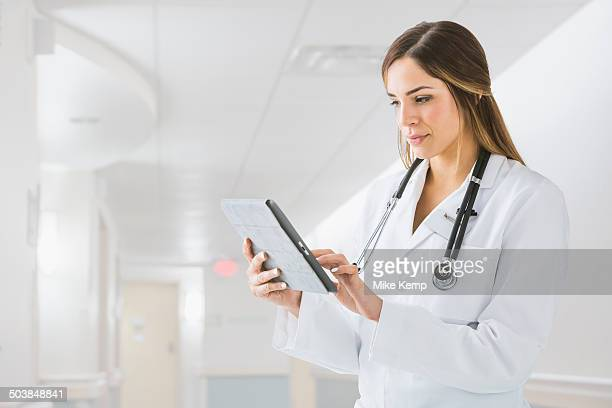 Mixed race doctor using digital tablet in hospital