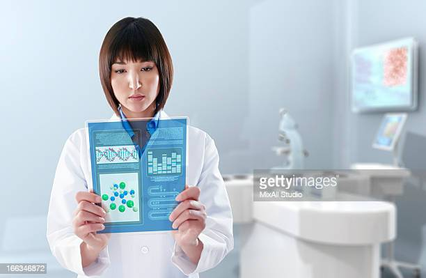 Mixed race doctor using digital tablet in laboratory