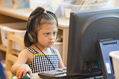 Mixed race Down syndrome student using computer