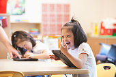 Mixed race Down syndrome student using tablet computer in classroom