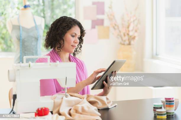 Mixed race dressmaker using digital tablet