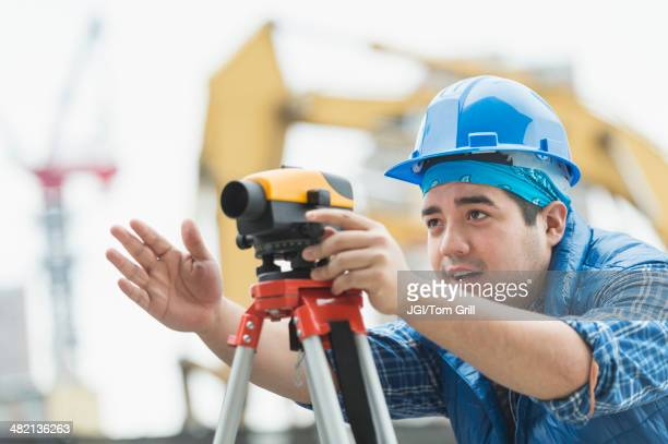 Mixed race engineer using theodolite at construction site