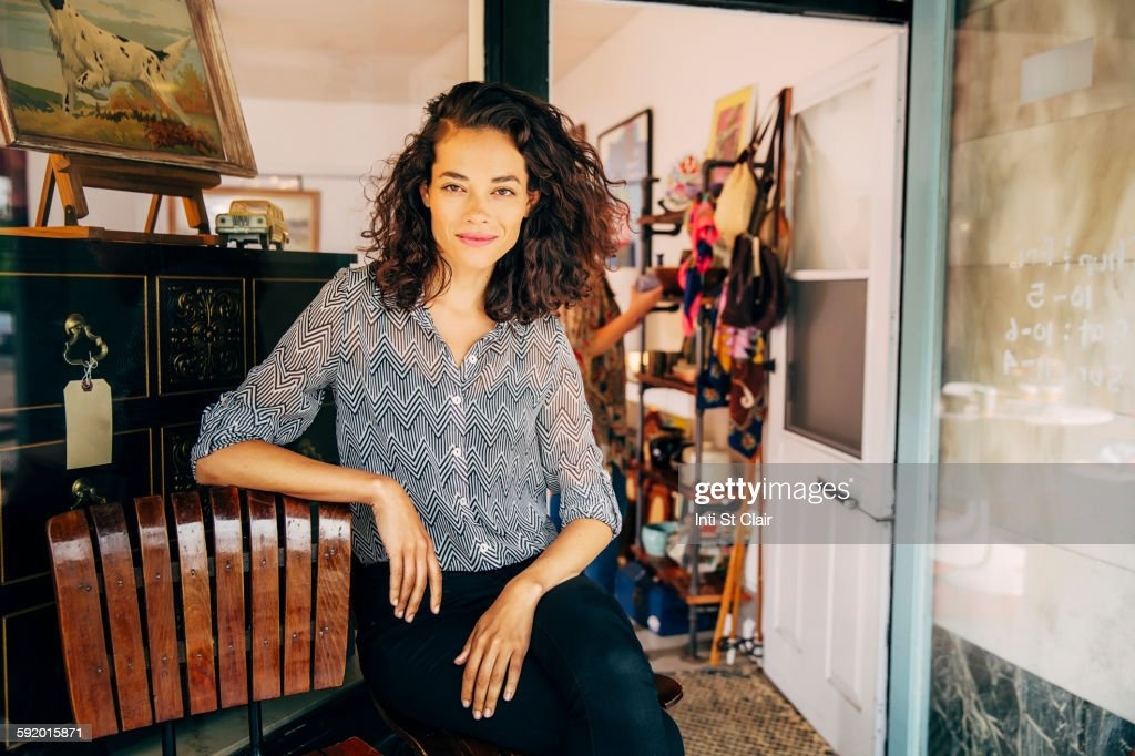 Mixed race entrepreneur sitting outside store