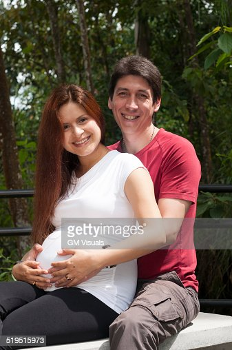 Mixed race expectant couple hugging outdoors