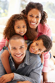Mixed race family at home smiling at camera
