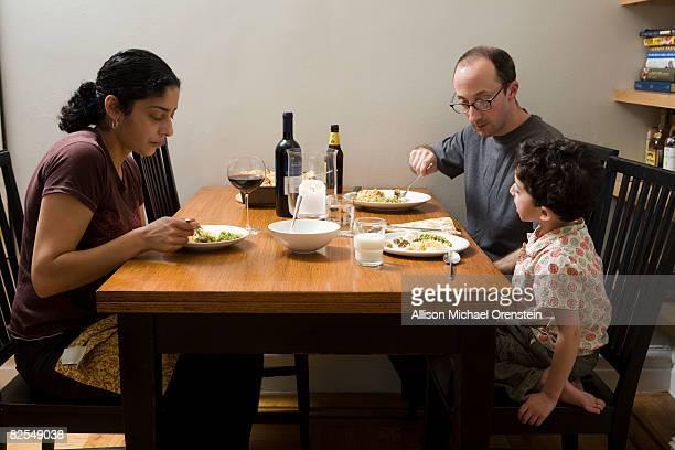 Mixed race family eating dinner
