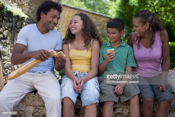 Mixed race family eating fresh bread