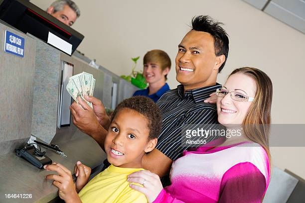 Mixed race family getting money at the bank