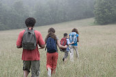 Mixed race family hiking with backpacks