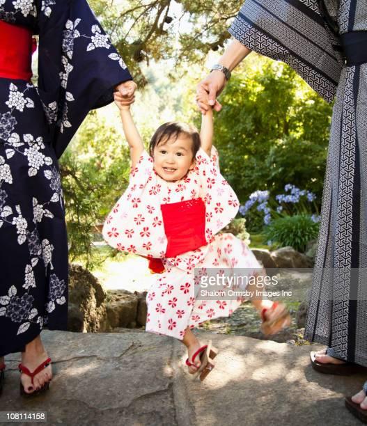 Girl ブランコから手を保護し、日本の着物を着ている