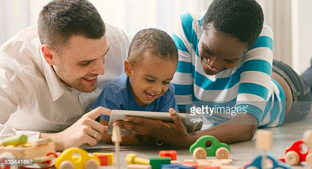 Mixed Race Family with child having fun with digital tablet.