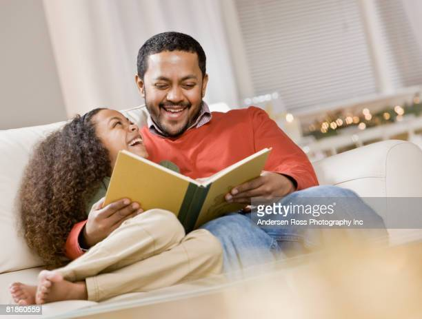 Mixed Race father and daughter reading
