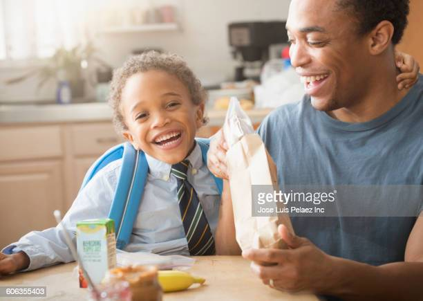 Mixed race father and son eating in kitchen