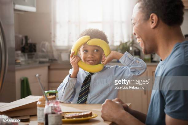 Mixed race father and son playing with food in kitchen