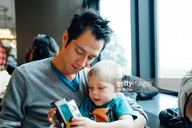 Mixed Race father and son reading menu in restaurant