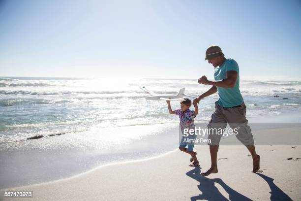 Mixed race father and son running with toy airplane on beach