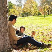 Mixed Race father and son sitting in park