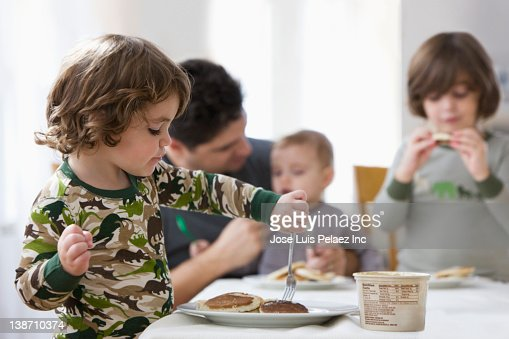 Mixed race father and sons eating breakfast together : Stock Photo