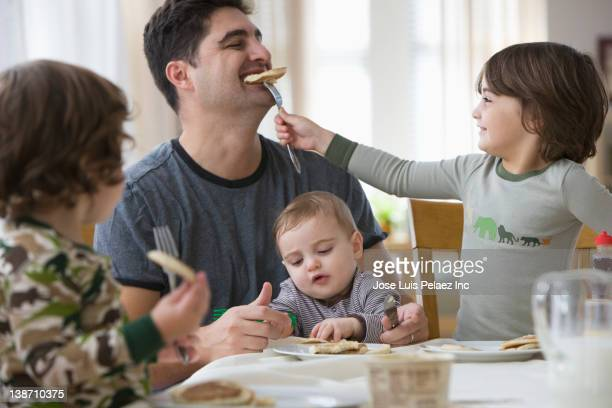 Mixed race father and sons eating breakfast together