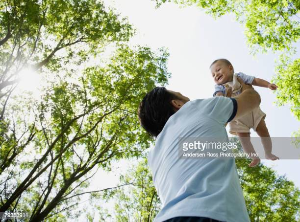 Mixed Race father holding baby in air