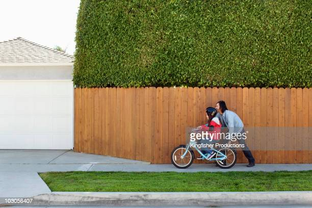 Mixed race father teaching daughter to ride bicycle