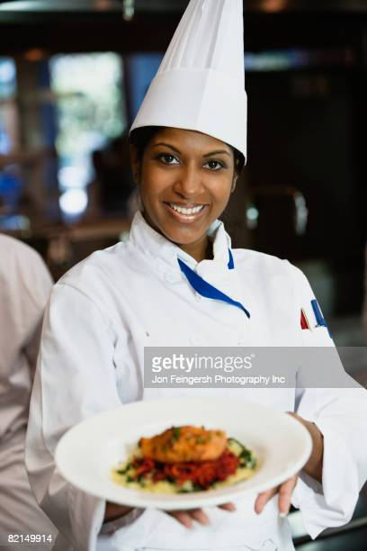 Mixed Race female chef holding plate of food