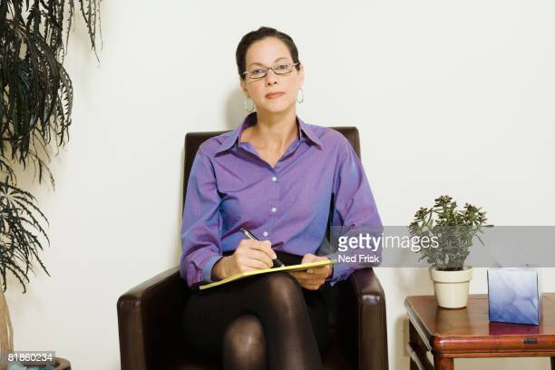 Mixed Race female psychiatrist holding notepad