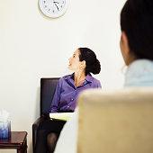 Mixed Race female psychiatrist looking at clock