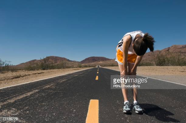 Mixed Race female runner stretching