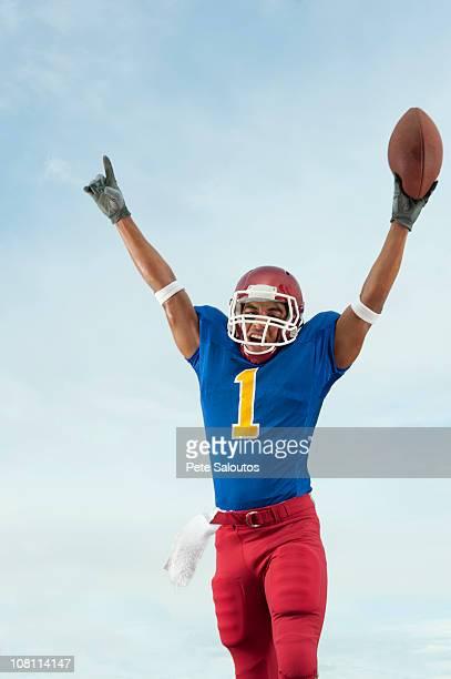 Jugador de fútbol con la raza mixta brazo de retención de fútbol americano
