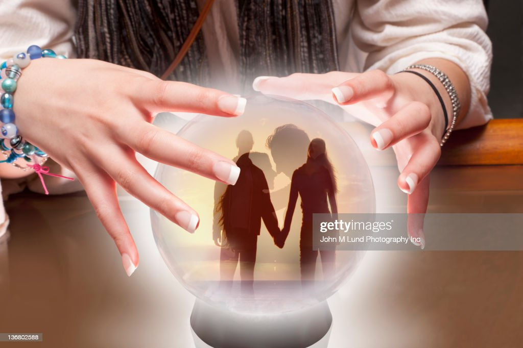 Mixed race fortune teller with crystal ball with people inside : Stock Photo