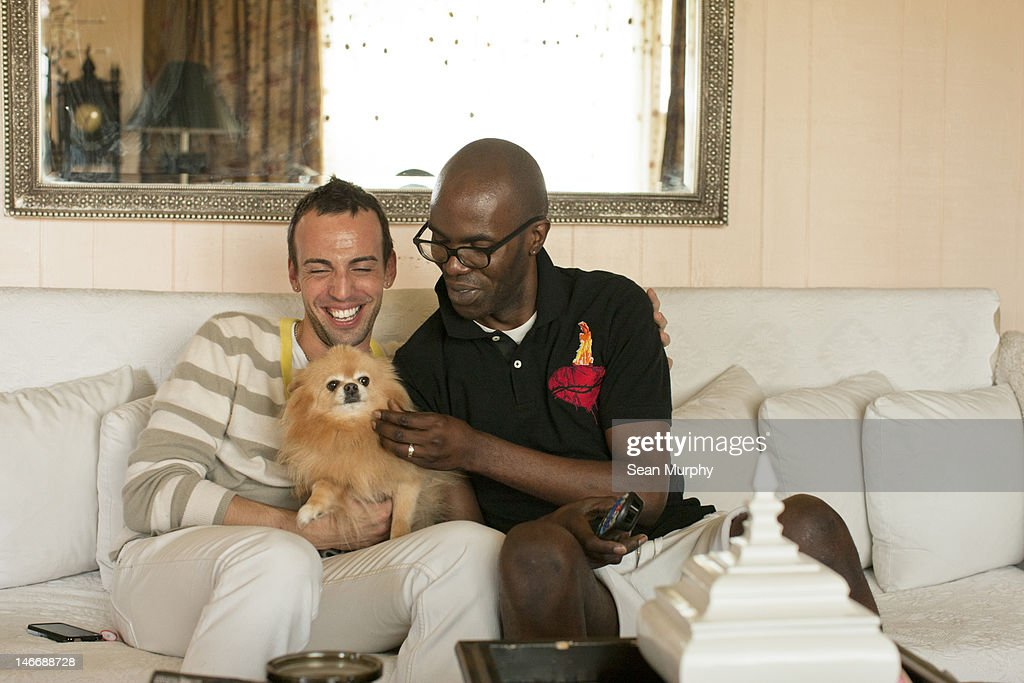 Mixed Race, Gay Couple Snuggling with Dog : Stock Photo