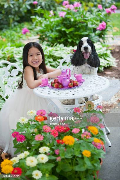Mixed race girl and dog having tea party in backyard