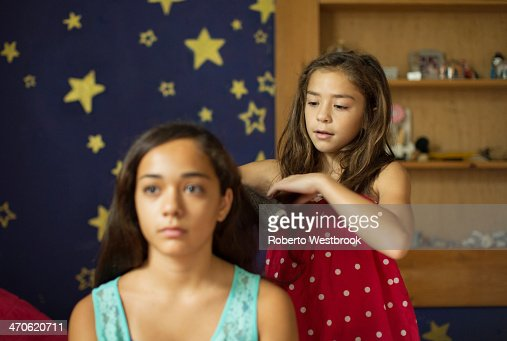Mixed race girl brushing sister's hair : Stock Photo
