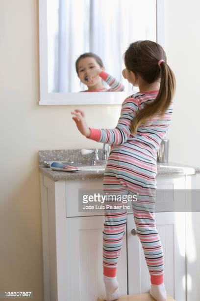 Mixed race girl brushing teeth