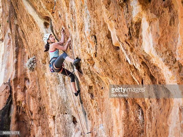 Mixed race girl climbing rock wall