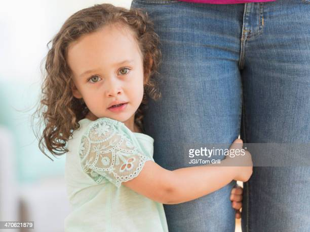 Mixed race girl clinging to mother's leg