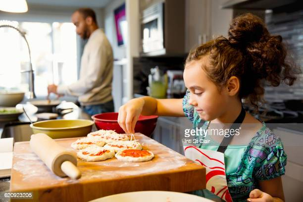 Mixed race girl cooking in kitchen