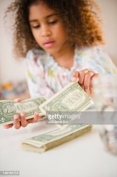 Mixed race girl counting dollar bills