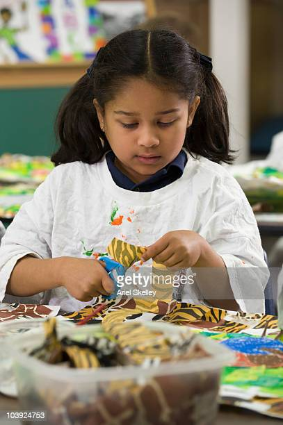 Mixed race girl cutting paper for art project