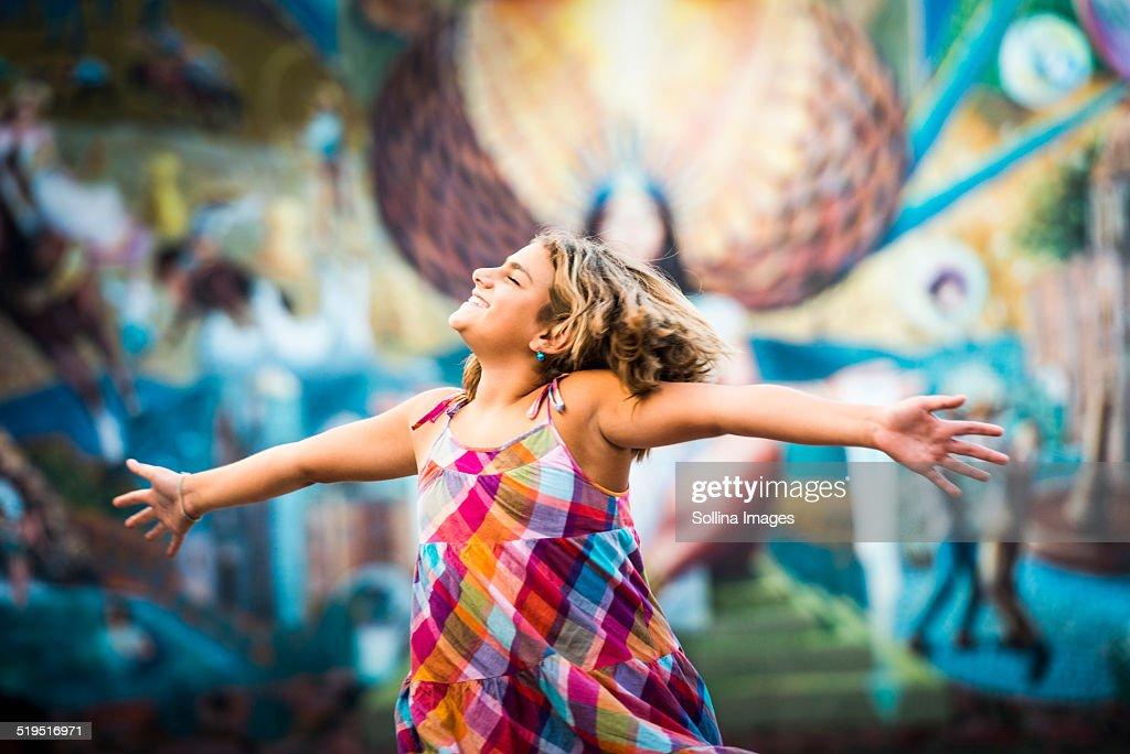 Mixed race girl dancing near urban rural