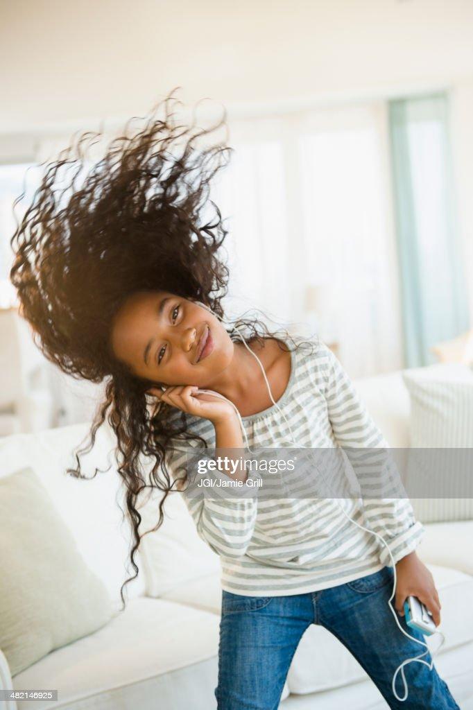 Mixed race girl dancing to headphones in living room